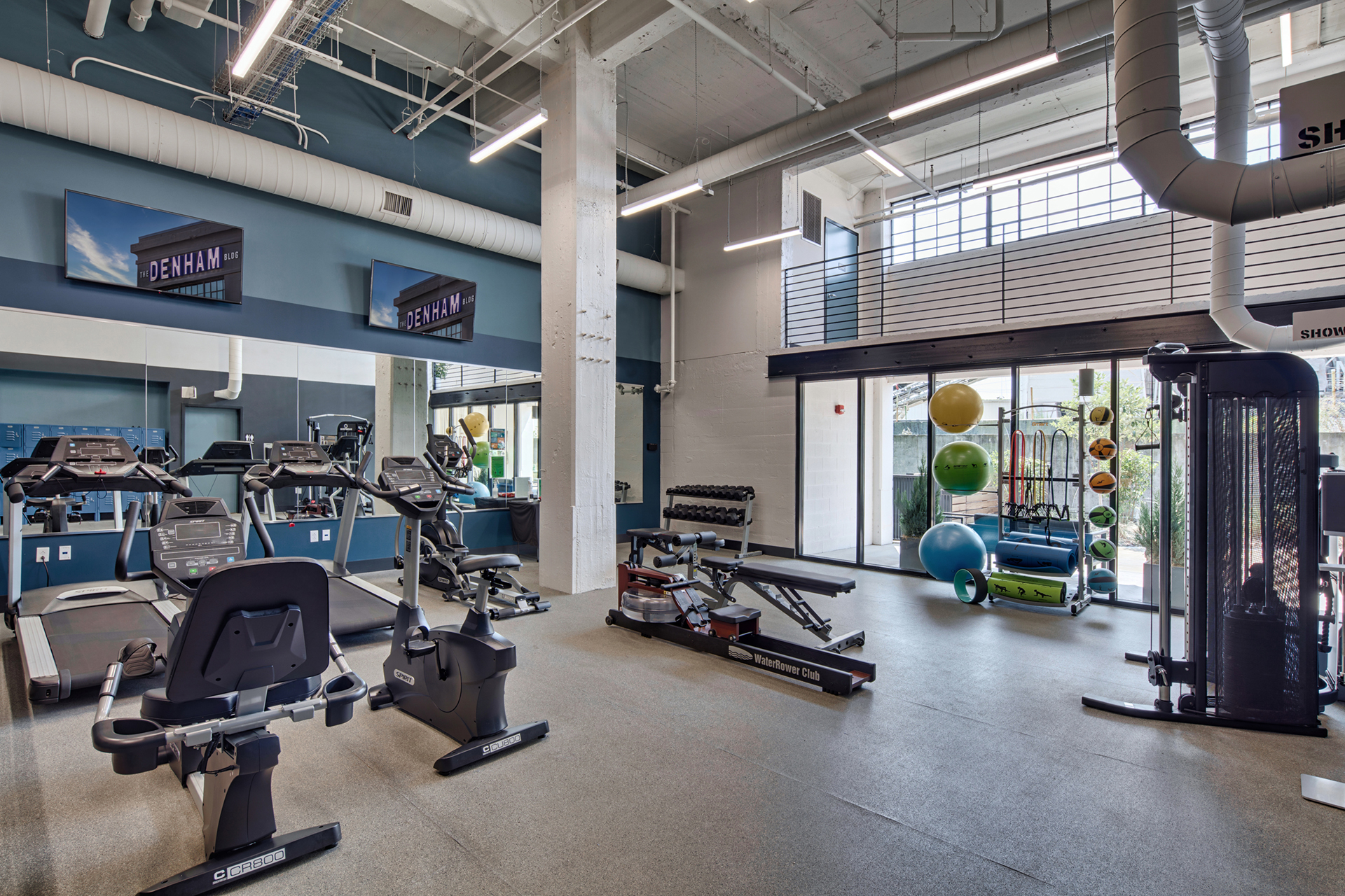 Fully equipped fitness center with cardio and weight machines at The Denham Building loft apartments for rent