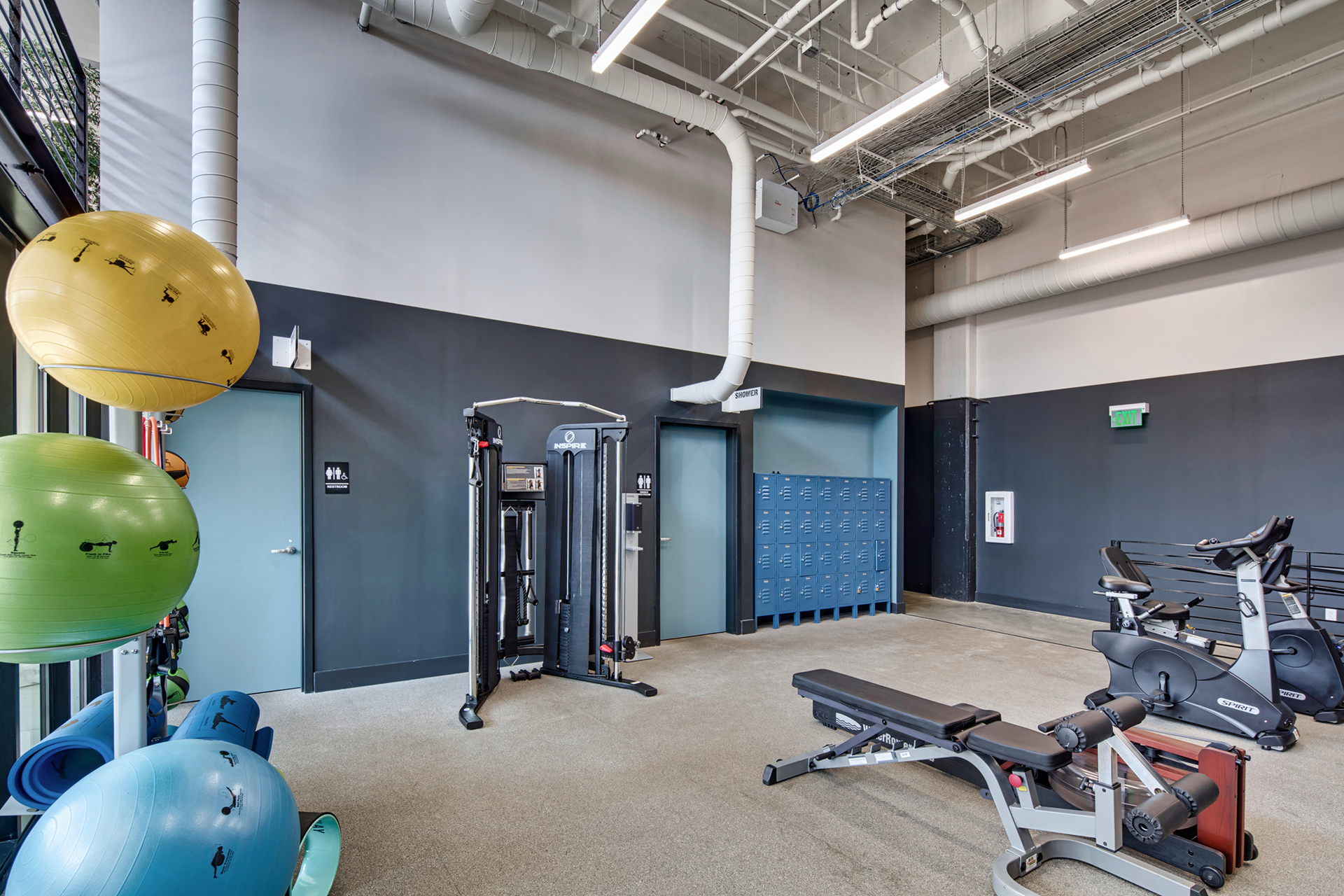 Fully equipped fitness center with cardio and weight equipment at The Denham Building loft apartments for rent