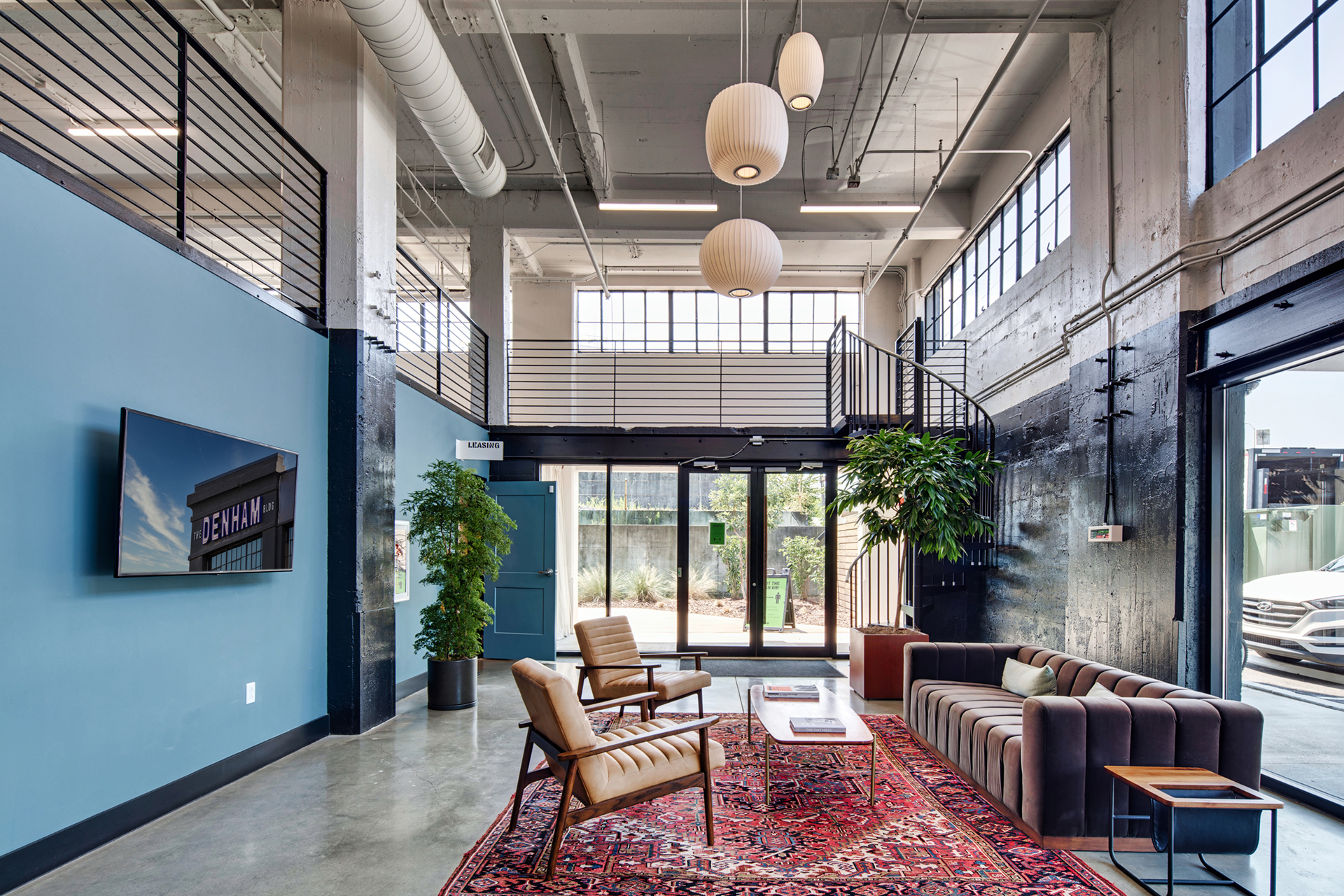 Large seating area with two chairs, sofa, indoor plants, and spiral staircase at The Denham Building loft apartments for rent