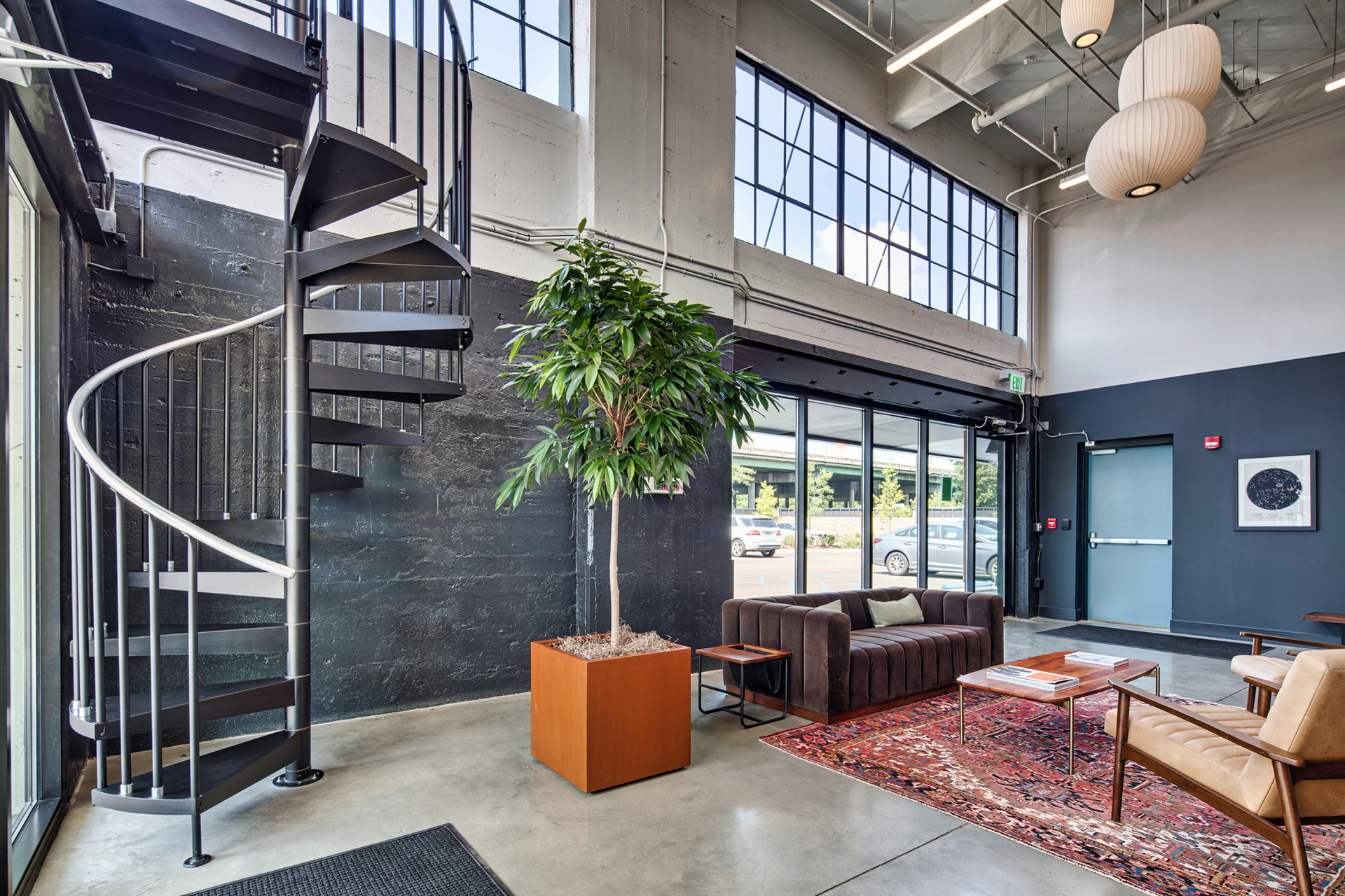Large seating area with indoor plants and spiral staircase at The Denham Building loft apartments for rent
