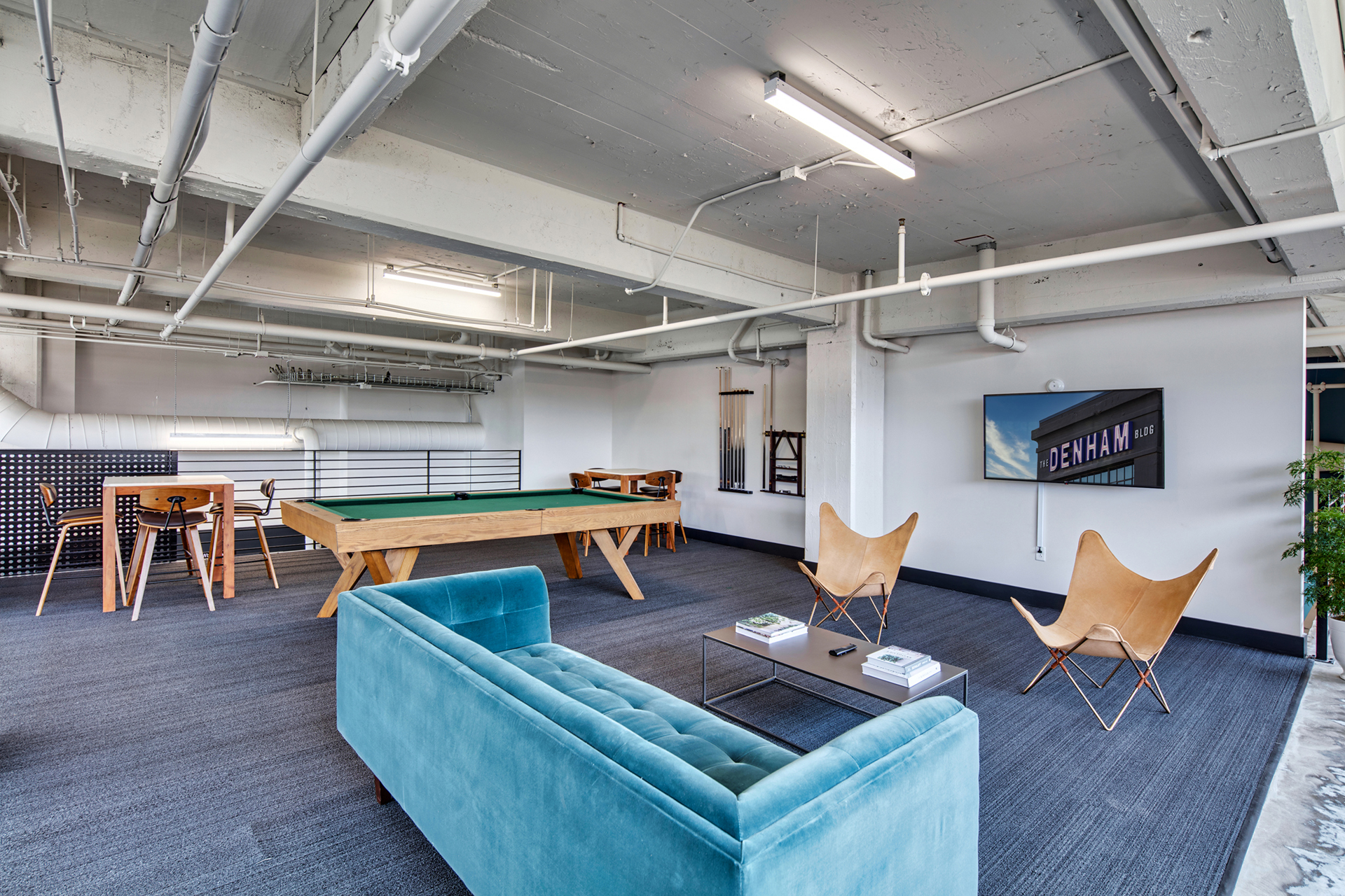 Community room with ample seating and pool table at The Denham Building loft apartments for rent in South Birmingham, AL