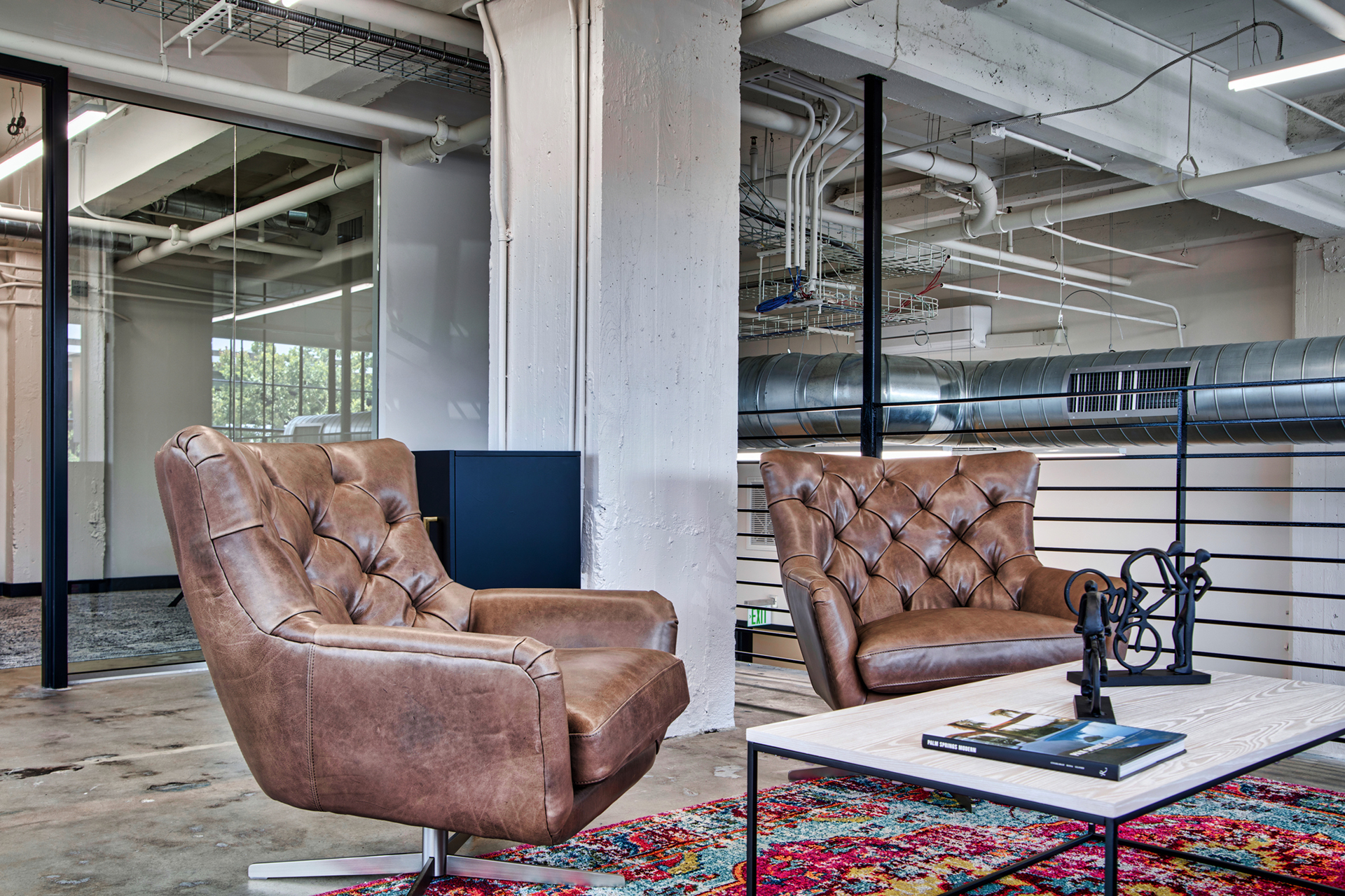 Seating area with two brown leather chairs at The Denham Building loft apartments for rent in South Birmingham, AL