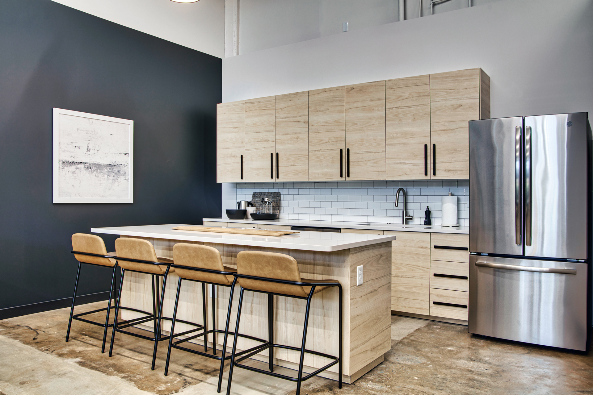 Community kitchen with island and refrigerator at The Denham Building loft apartments for rent