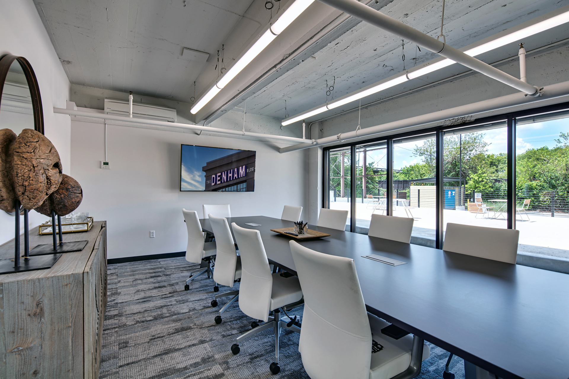 Conference room with large table and multiple white office chairs for working professionals at The Denham Building loft apartments for rent
