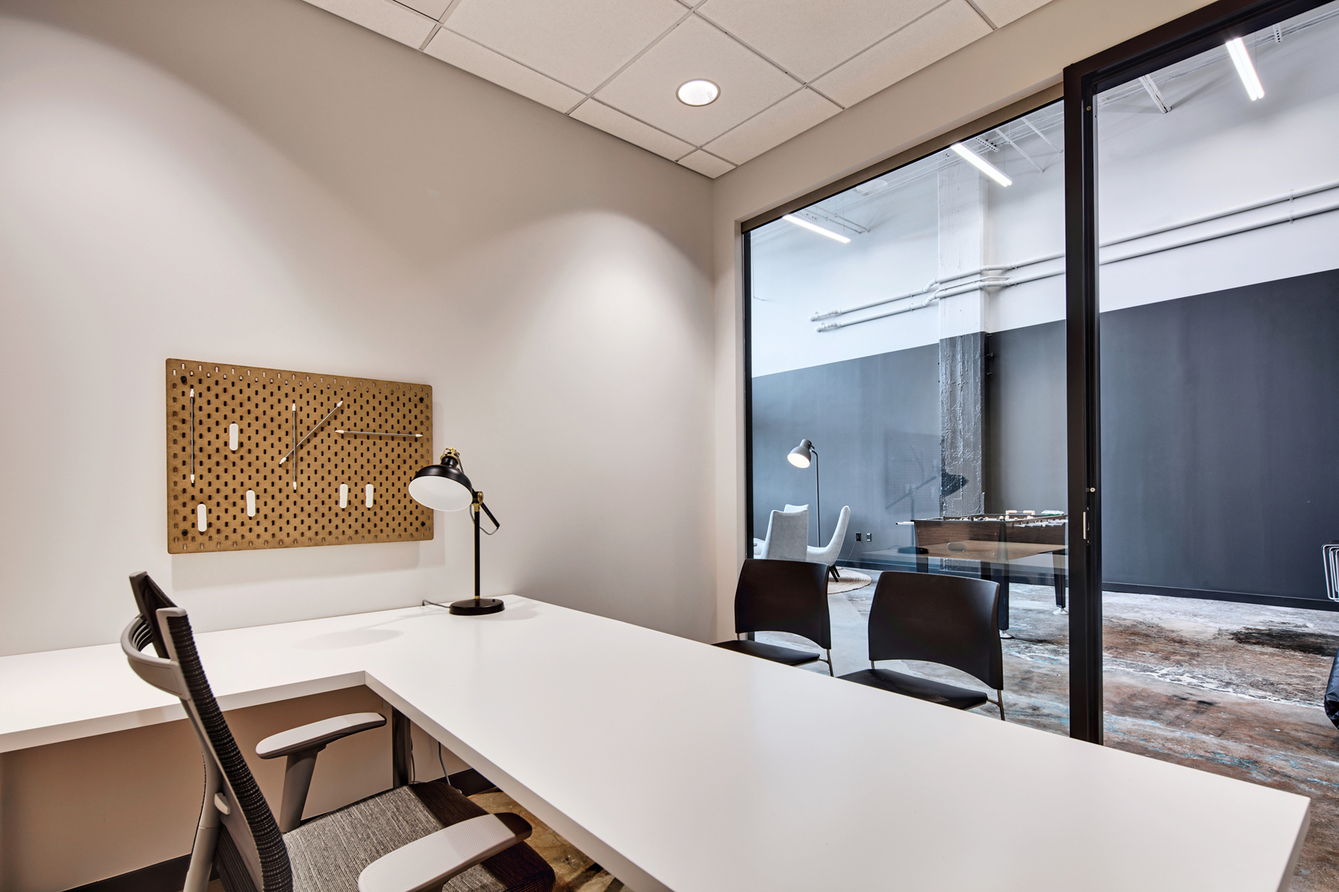 Office space with white desk and three chairs for working professionals at The Denham Building loft apartments for rent