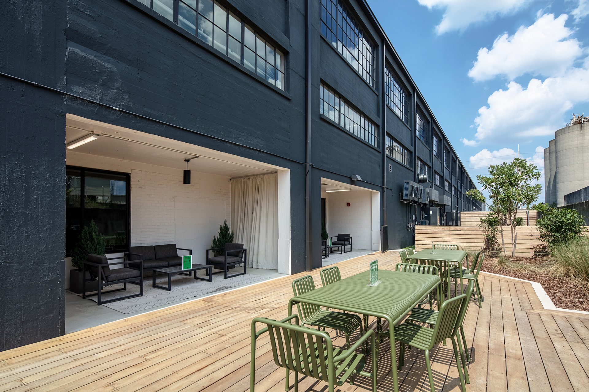 Outdoor seating area with tables and chairs at The Denham Building loft apartments for rent in Birmingham, AL