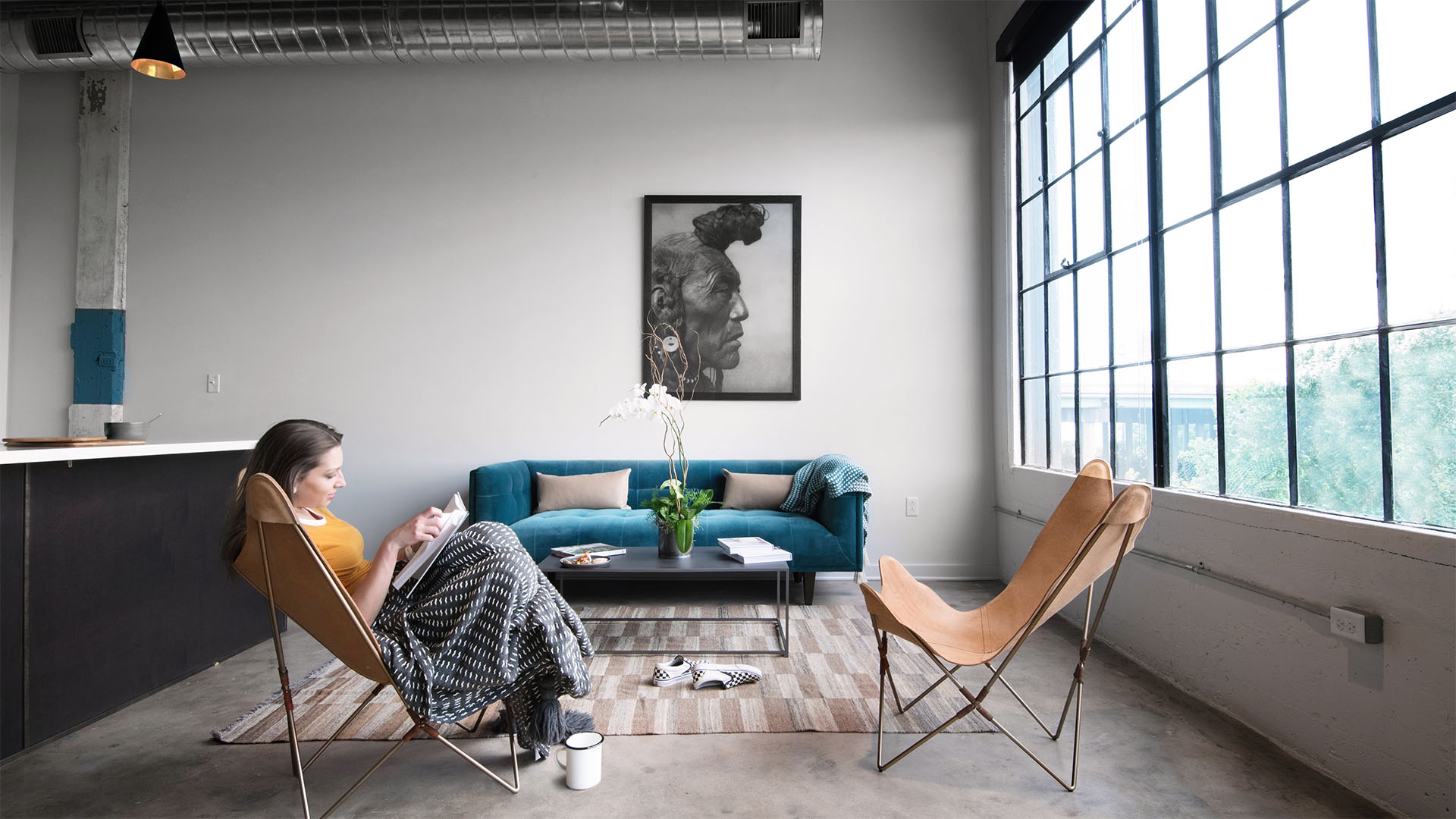 Living room with ample seating and floor to ceiling windows at The Denham Building loft apartments for rent in South Birmingham, AL