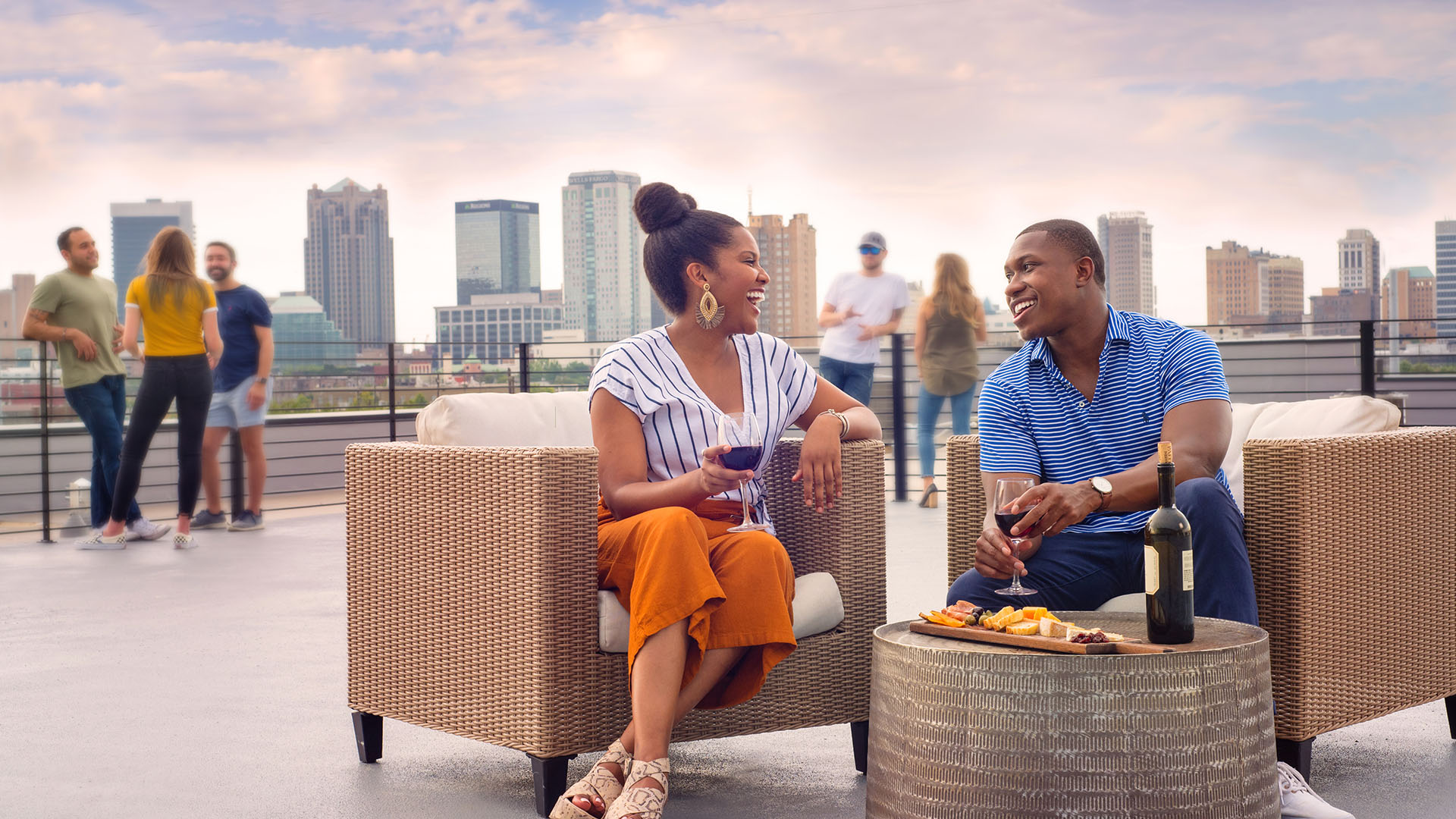 People enjoying food and drinks on the rooftop lounge at The Denham Building loft apartments for rent in South Birmingham, AL