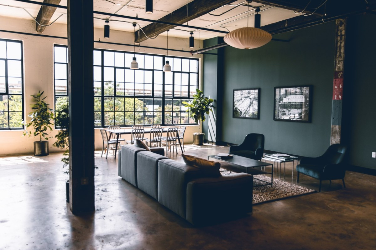 On-site office environment with couches and a table with chairs at Denham Lofts